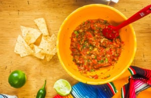 A yellow bowl of cherry tomato salsa and tortilla chips.