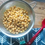Cooked chickpeas in a metal strainer with a blue napkin and a red rubber spatula.