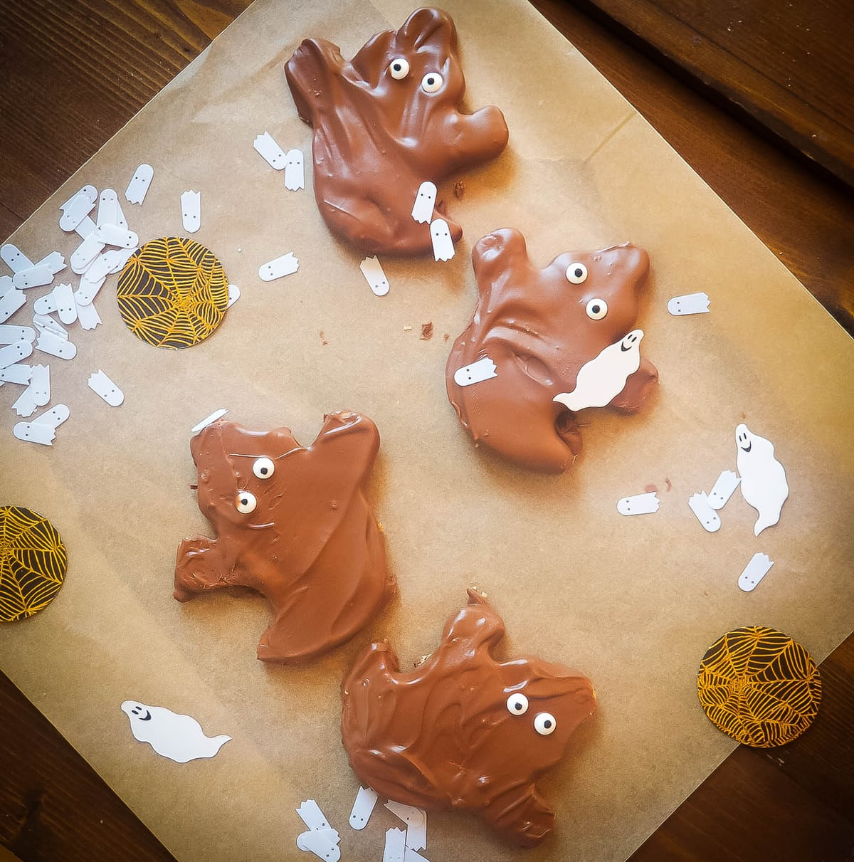 Four homemade Reese's peanut butter cup ghosts on brown parchment paper with Halloween confetti.