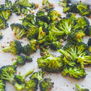 A cookie sheet with roasted broccoli and garlic on it.