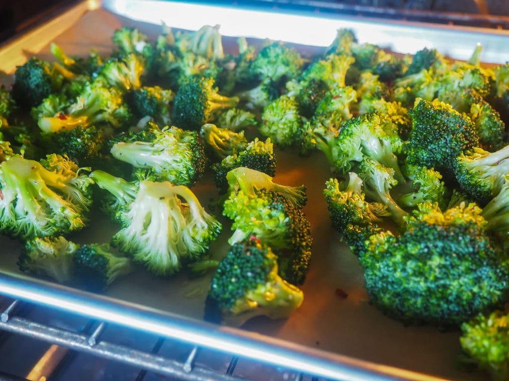 A cookie sheet in the oven with broccoli roasting on it.
