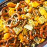 A close-up of a football shaped bowl of party mix with pretzels, chex, and goldfish.