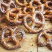Seasoned pretzels spread out on a wooden board.