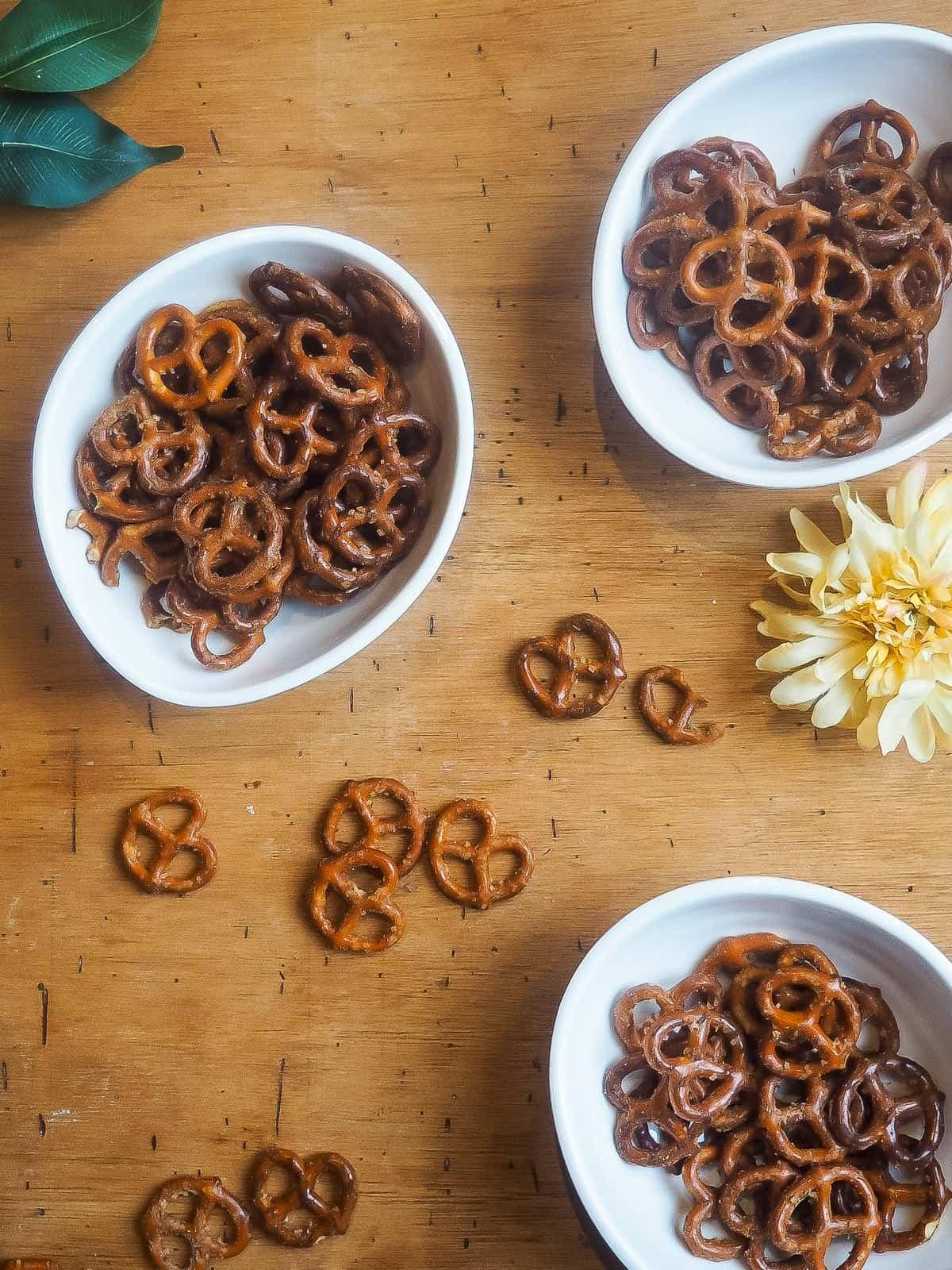 Seasoned pretzels in three white bowls on a wooden board.