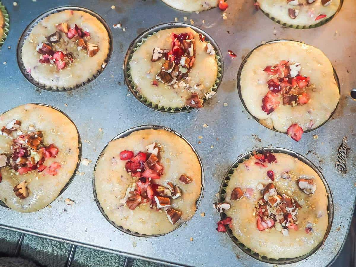 Cranberry, orange, and pecan muffins baking in the oven with sugar on them.