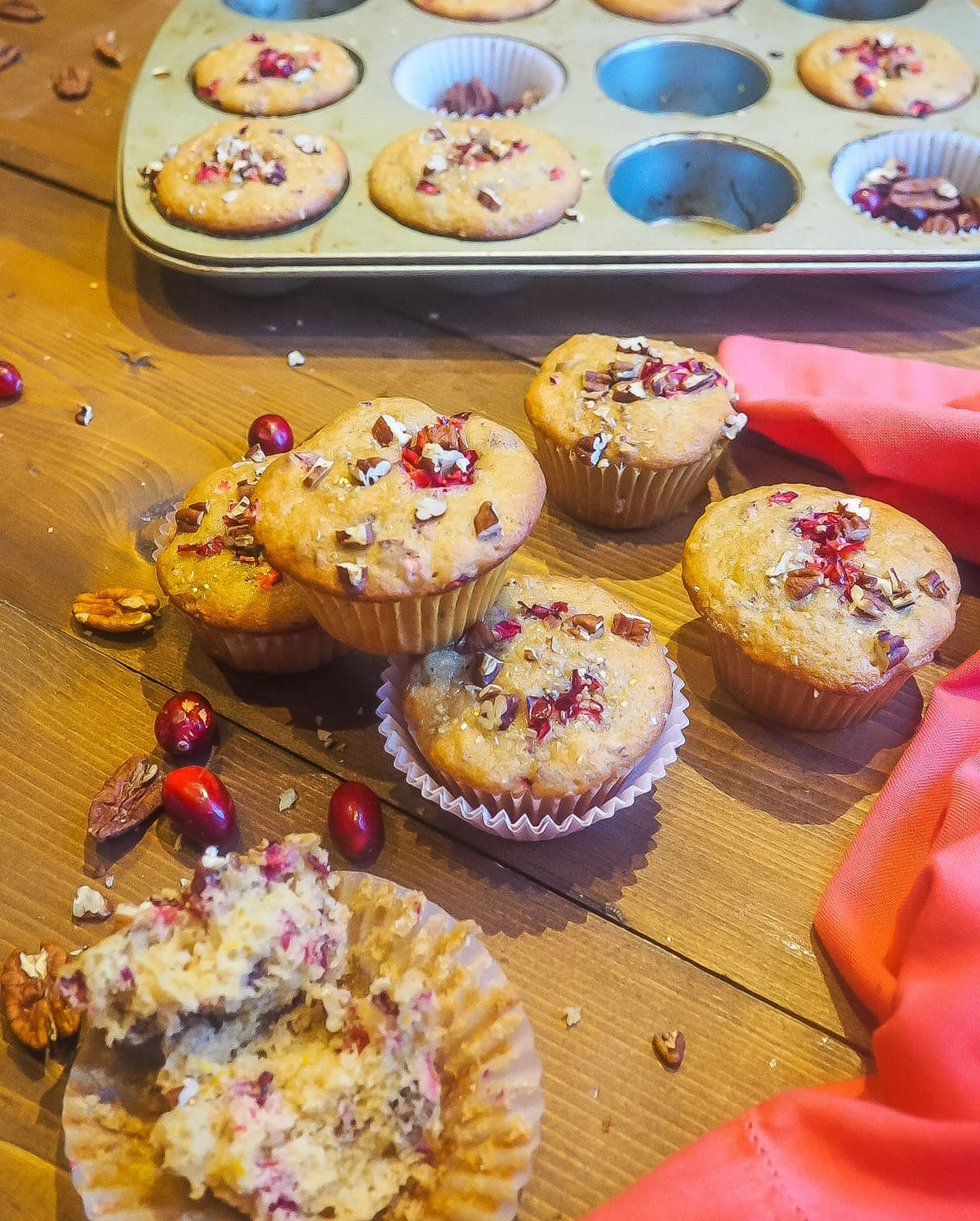 Freshly baked cranberry orange muffins sprinkled with pecans stacked in front of a muffin tin.