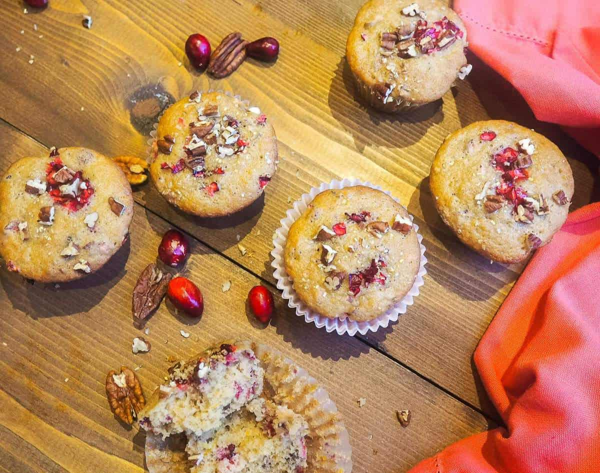 Freshly baked cranberry orange muffins sprinkled with pecans spread out on a wood board.