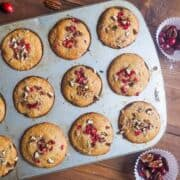 Freshly baked cranberry orange muffins sprinkled with pecans still in the muffin tin.