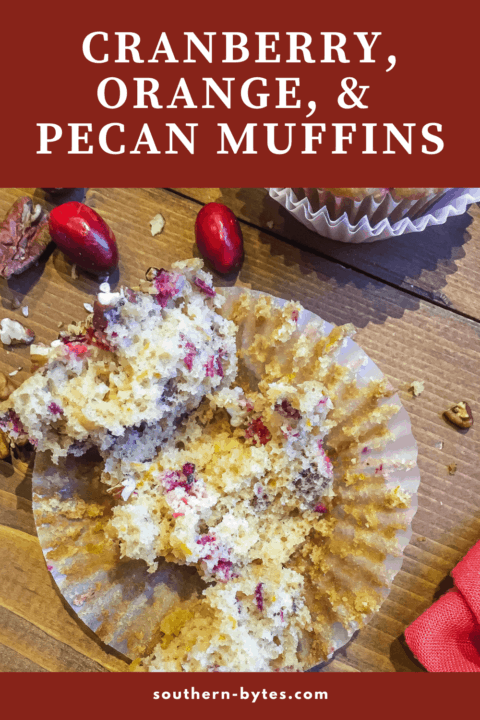 A pin image of a freshly baked cranberry orange muffin sprinkled with pecans, ripped open in the paper.