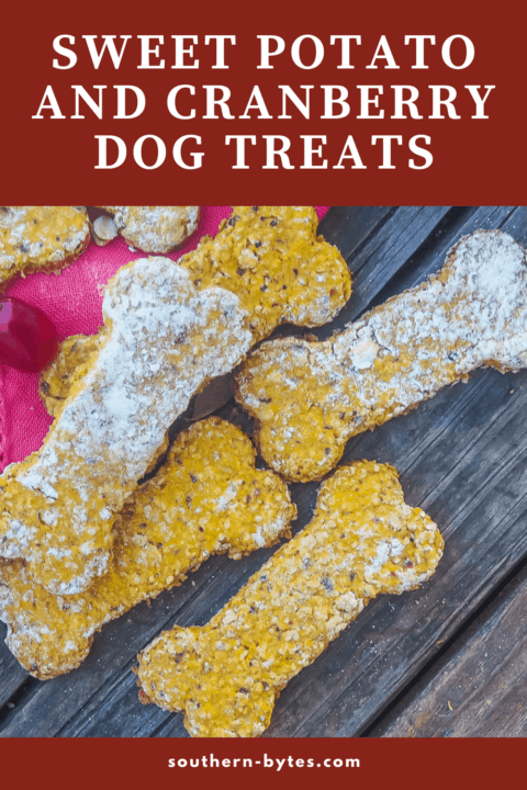 A pin image of bone shaped sweet potato and cranberry dog treats on a wood board.