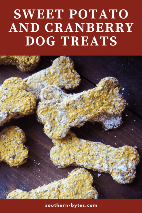 A pin image of bone shaped sweet potato and cranberry dog treats on a dark board.