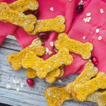 Bone shaped dog treats on a pink napkin with cranberries and oats scattered on a wood floor.