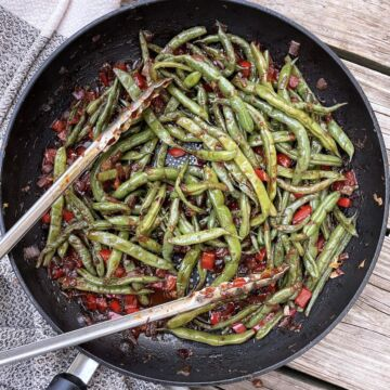 A white serving dish filled with green beans, chopped bell pepper, and onion.