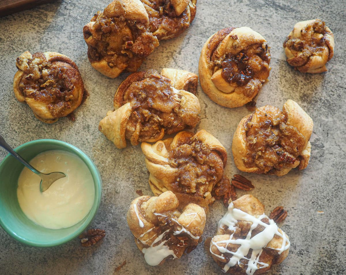 Praline crunch cinnamon knots on a gray board and a bowl of icing.