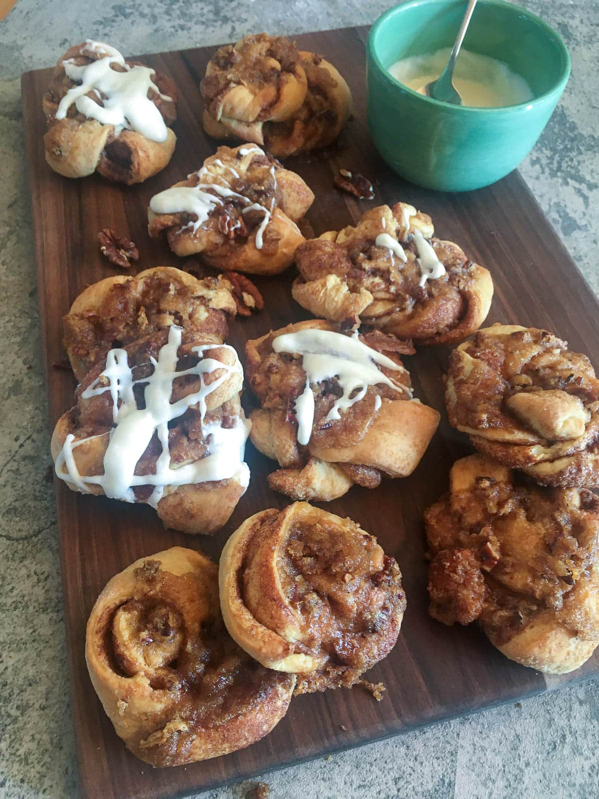 Praline crunch cinnamon rolls on a brown cutting board and a green bowl of icing.