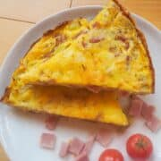 Two slices of ham and cheese frittata stacked on a white plate.