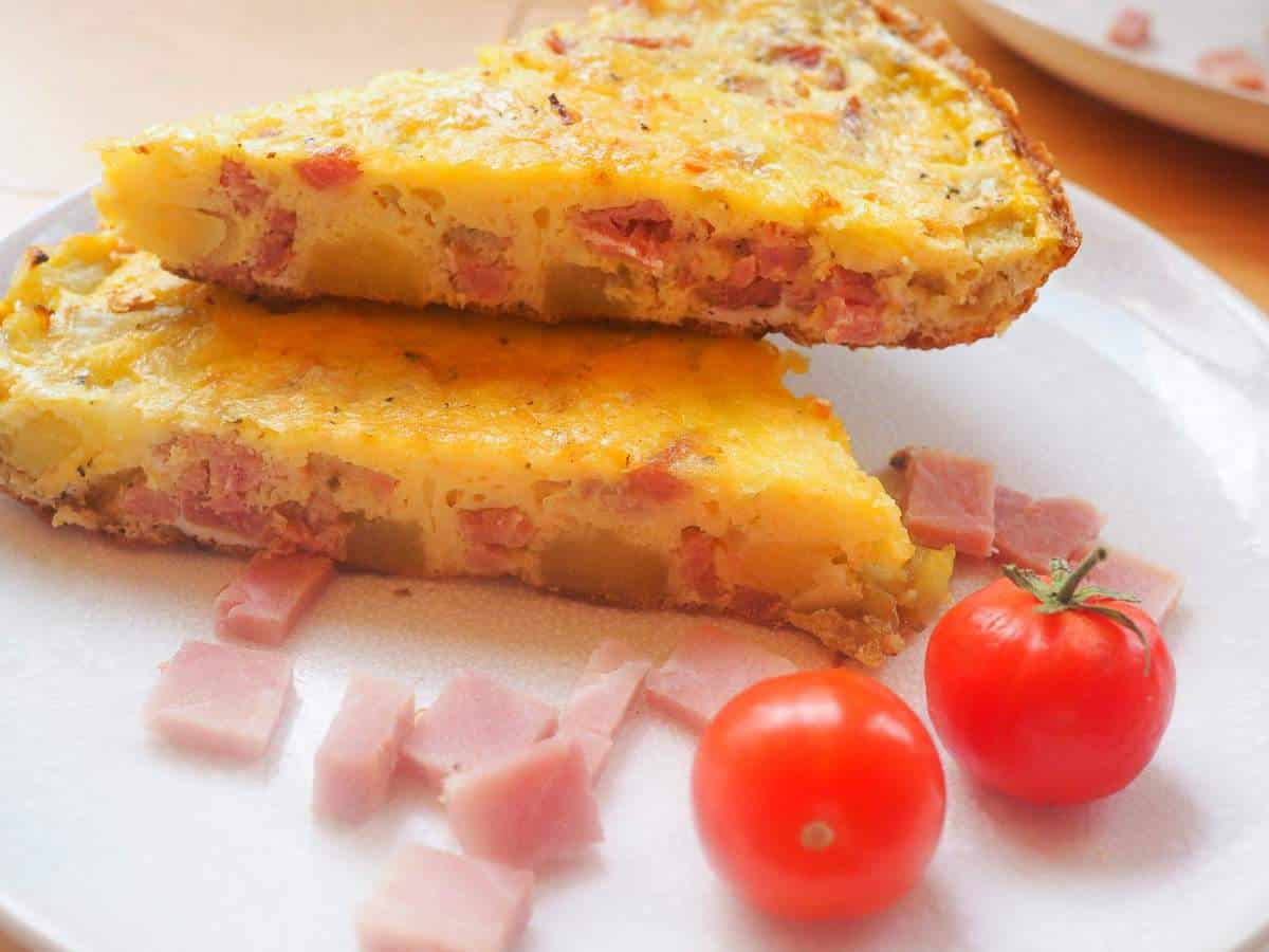 Two slices of ham and gruyere frittata with some fresh tomatoes stacked on a white plate.