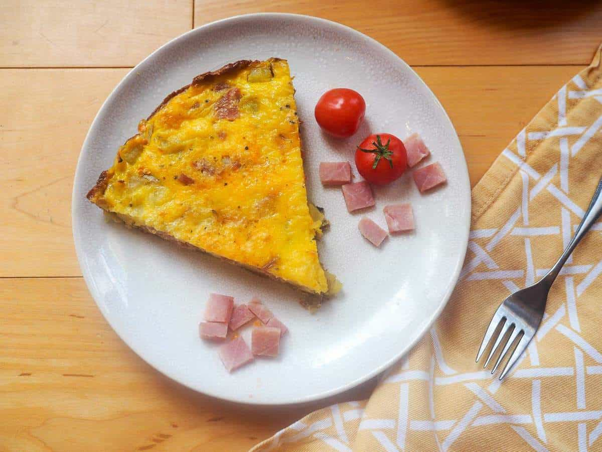 A slice of ham and gruyere frittata with some fresh tomatoes on a white plate.