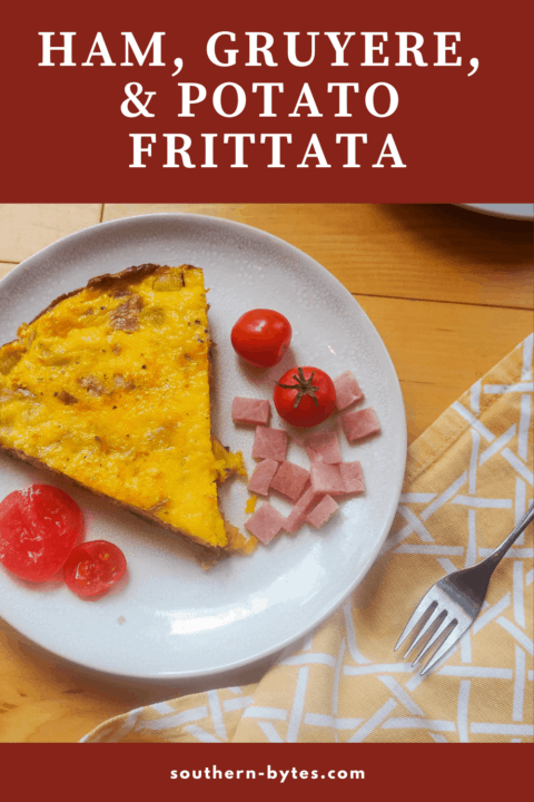 A pin image of a slice of ham and gruyere frittata with some fresh tomatoes on a white plate.
