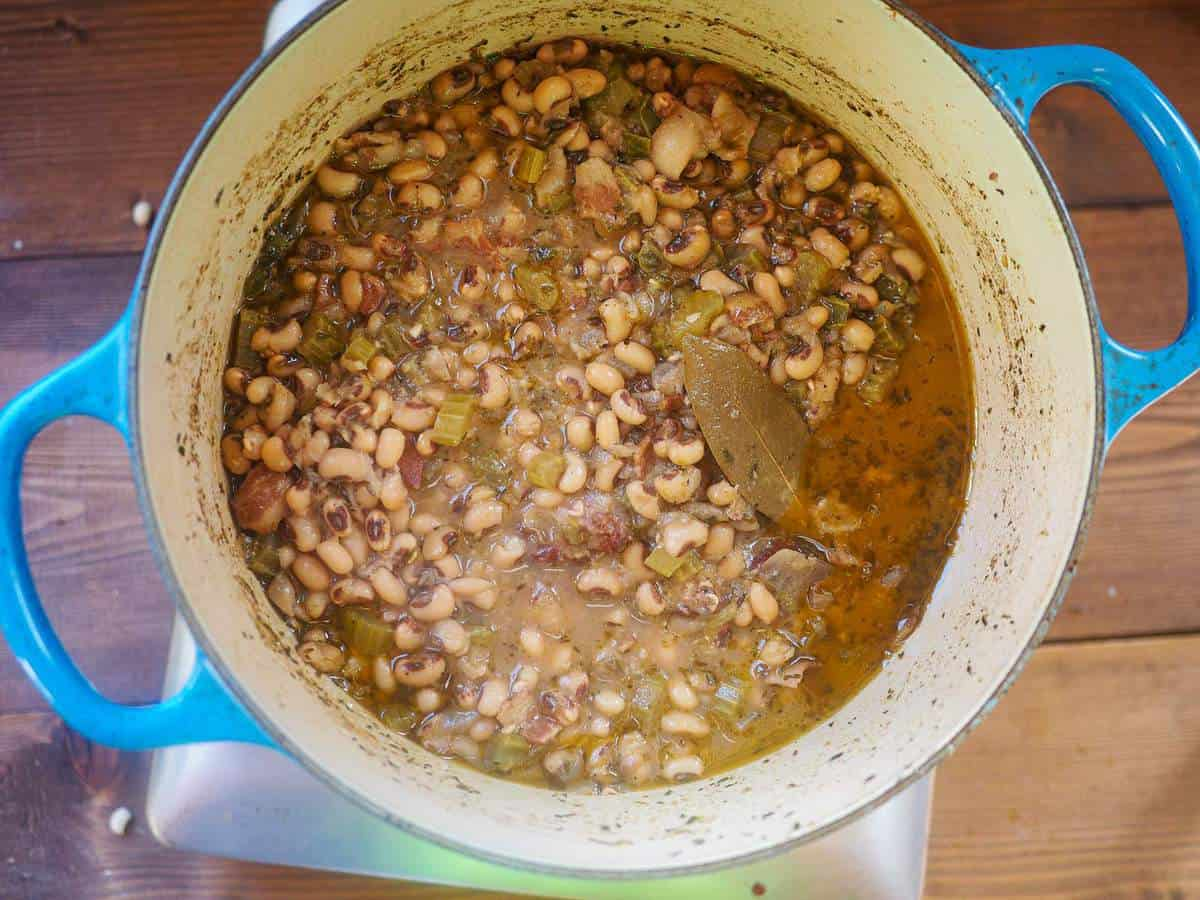 A blue pot filled with cooked hoppin john black eyed peas.