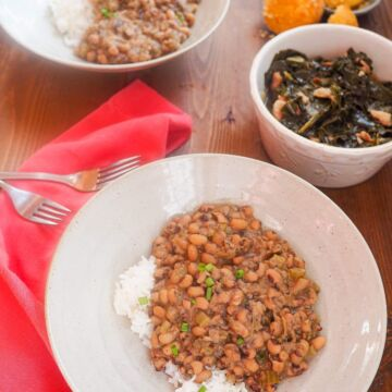Two bowls of hoppin john black eyed peas with a bowl of collard greens and some corn muffins.