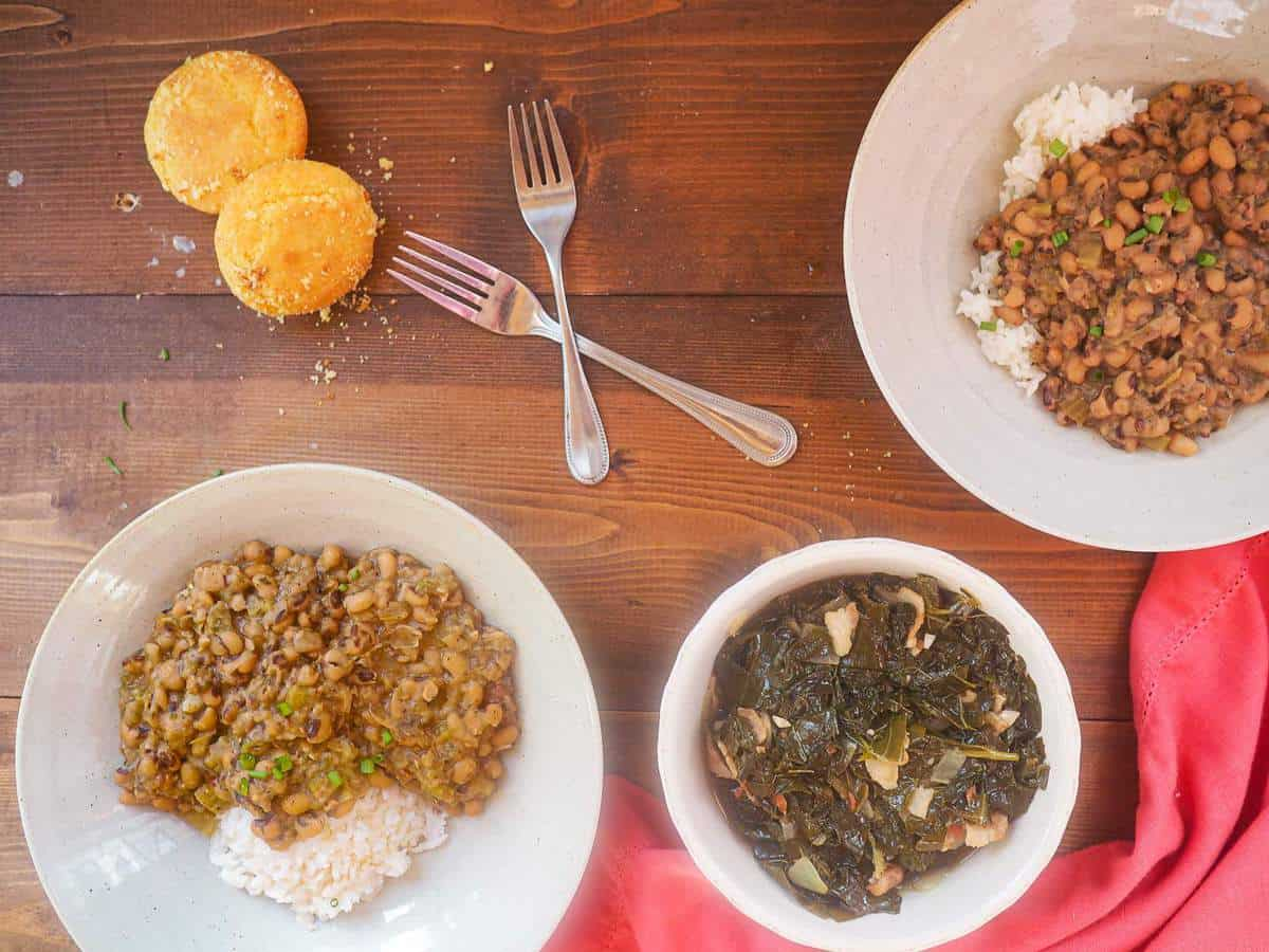 Two bowls of hoppin john black eyed peas with a bowl of collard greens, two forks, and some corn muffins.