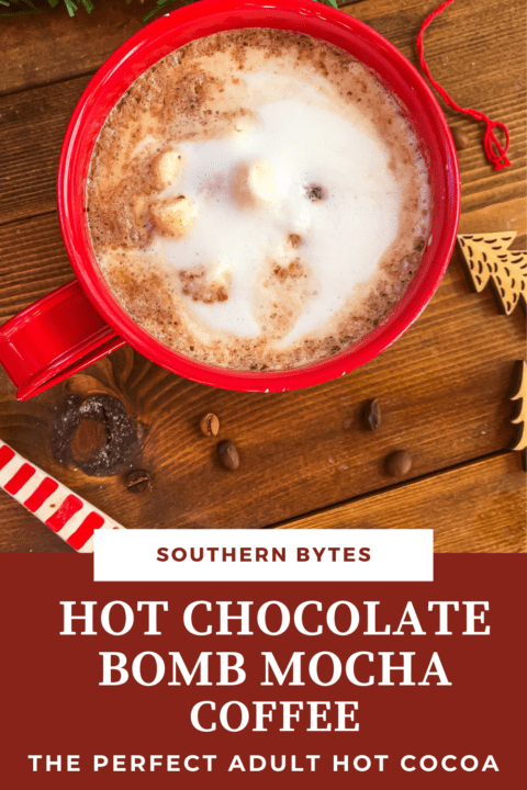 A pin image of a red mug of hot chocolate topped with steamed milk on a wooden background surrounded by spilled coffee beans.
