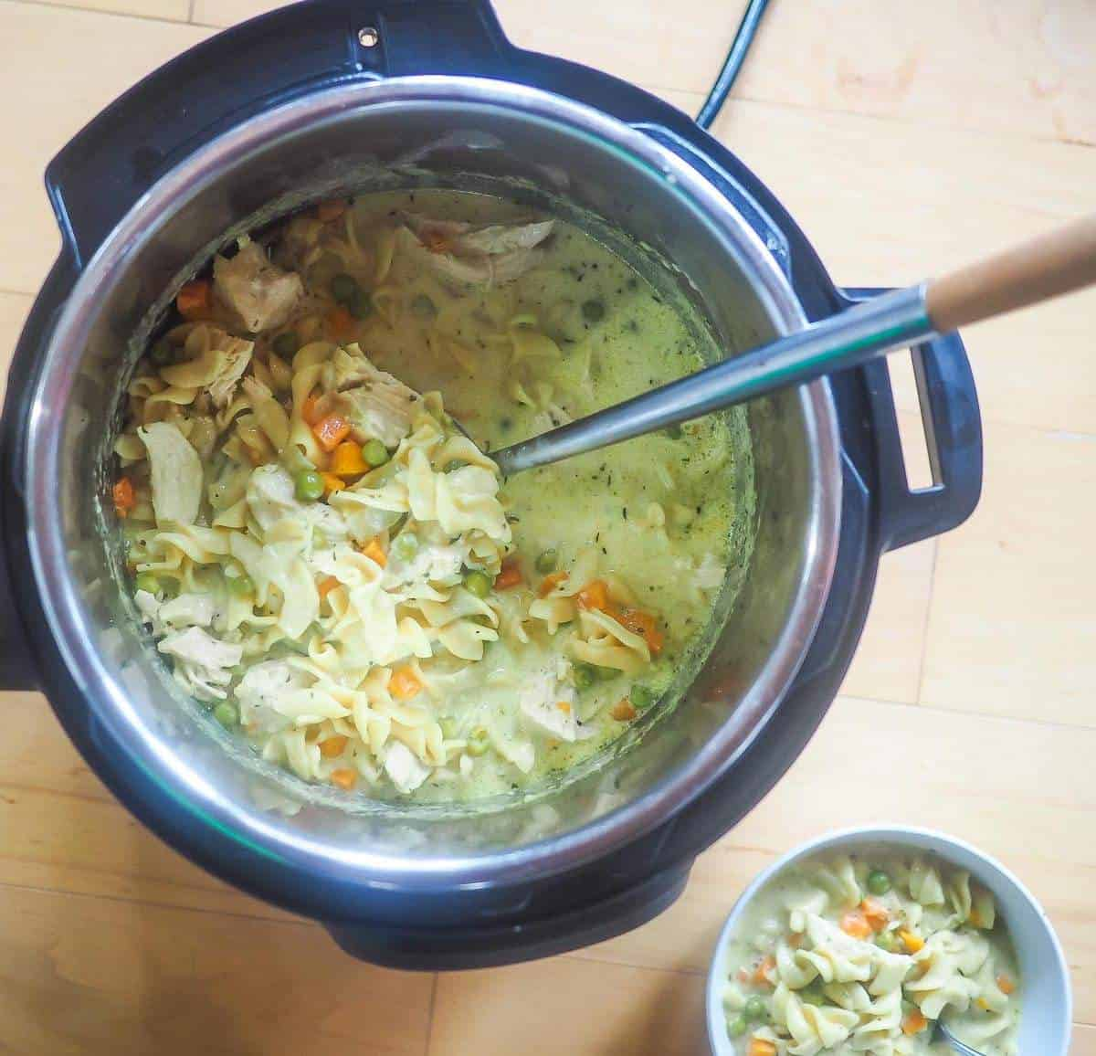 An instant pot of chicken pot pie soup and a small bowl next to it.