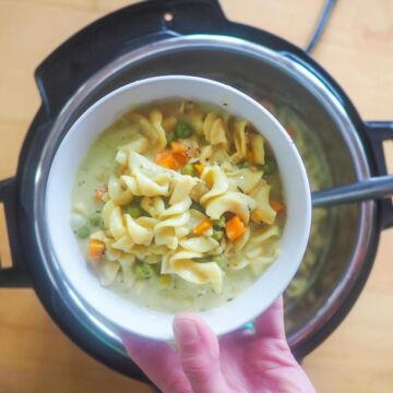 A bowl of chicken pot pie soup over an instant pot.