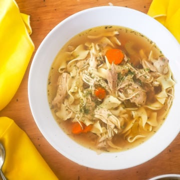 A white bowl of chicken noodle soup with yellow napkins.