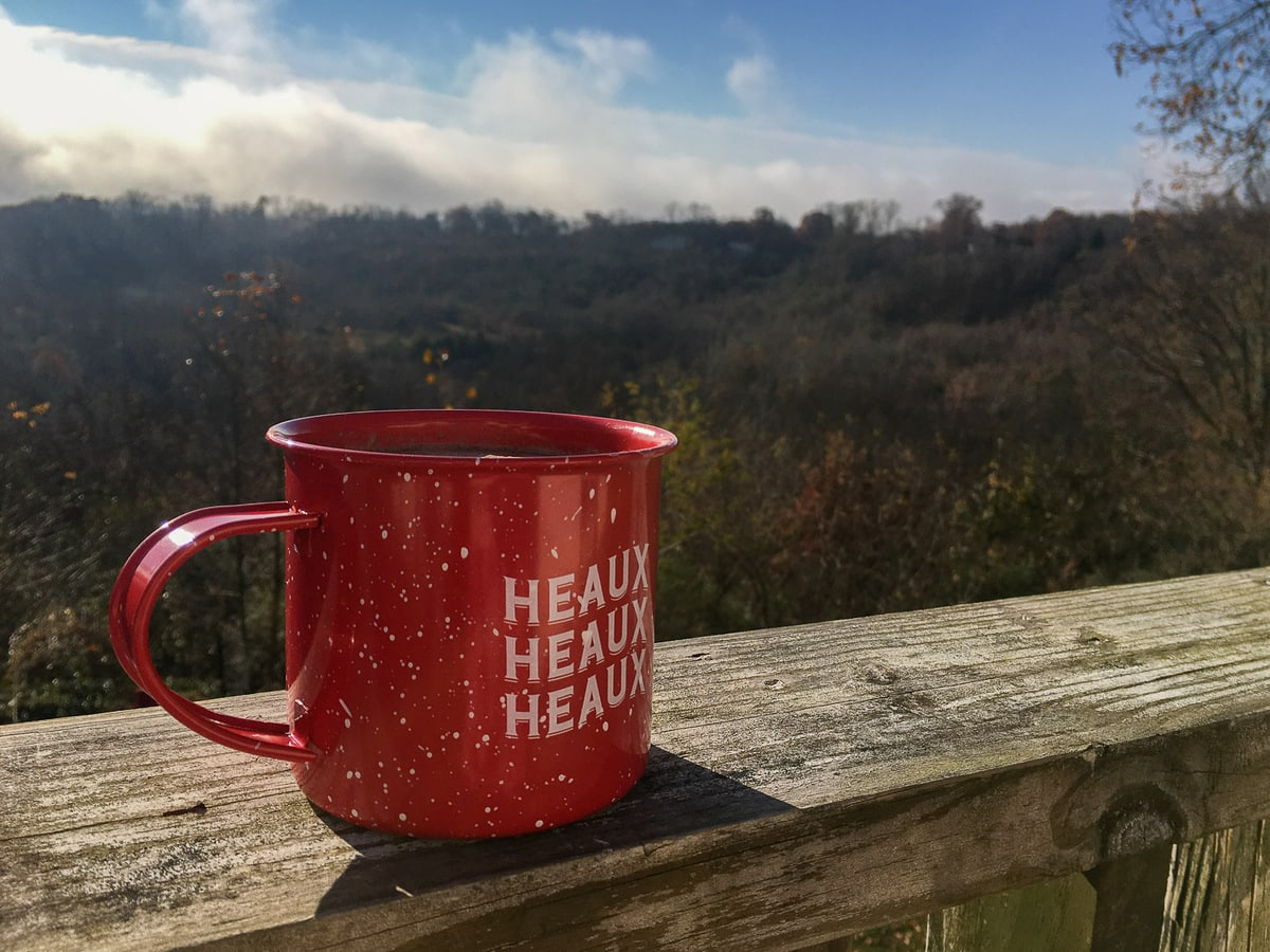 A red mug of cocoa on a porch overlooking the woods.
