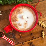 A red mug of hot chocolate topped with steamed milk on a wooden background surrounded by spilled coffee beans.