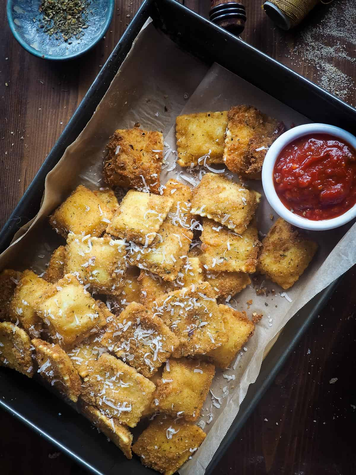 Fried ravioli in a baking pan with a bowl of sauce and a bowl of pizza seasoning.