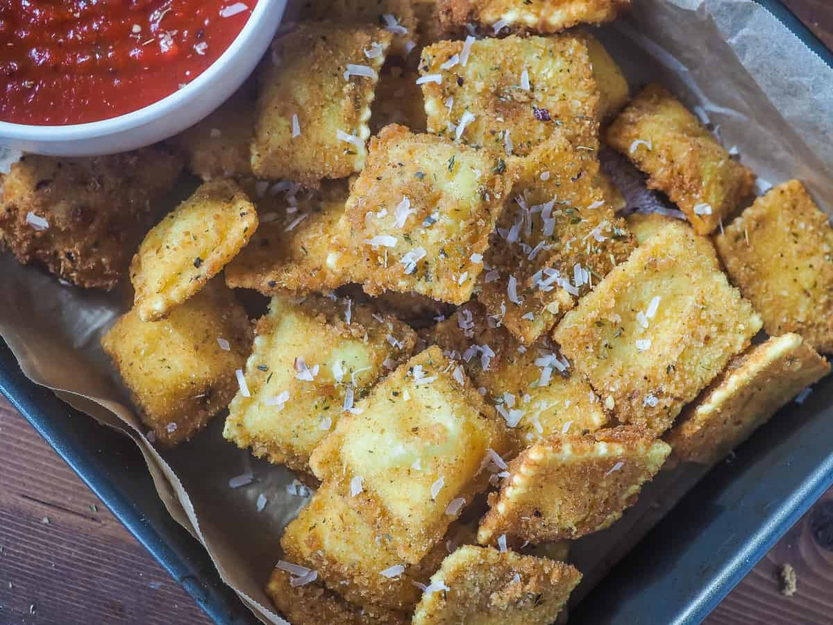 Zoomed in on fried ravioli in a baking pan with a bowl of sauce.