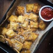 Toasted ravioli in a baking pan with a bowl of sauce.