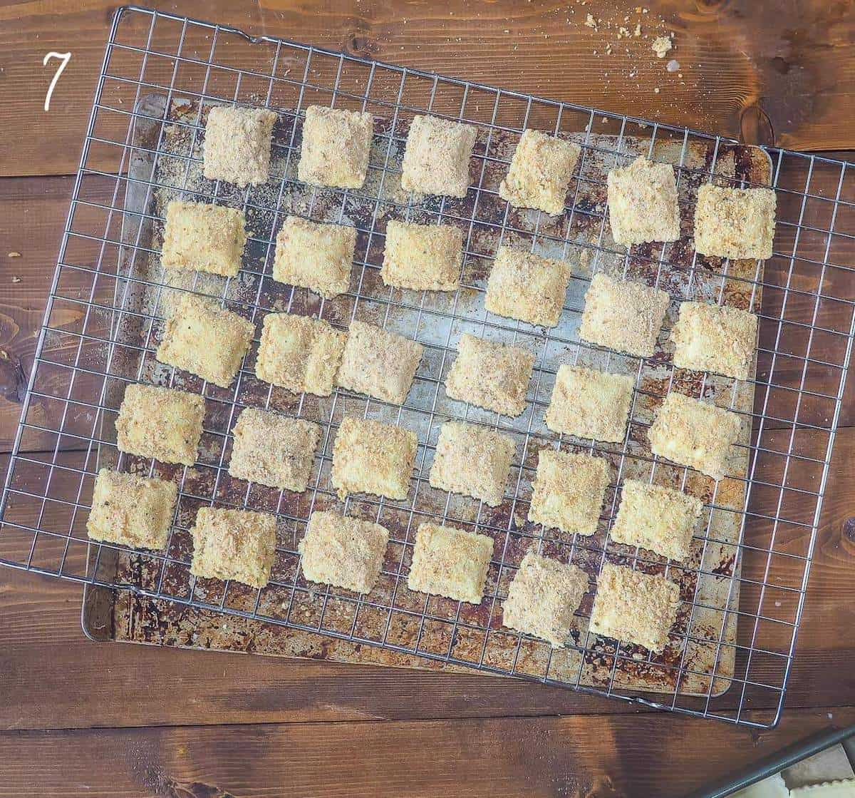 Breaded but uncooked ravioli on a cookie rack.