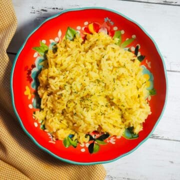 A red bowl of rice pilaf on a wood board with a yellow napkin.