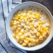 A white bowl of creamed corn.