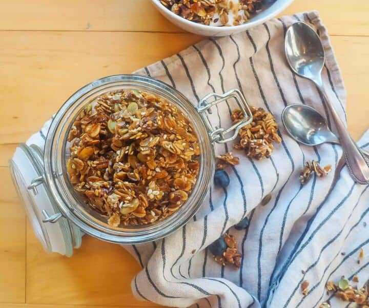 A jar of homemade granola and two small spoons.