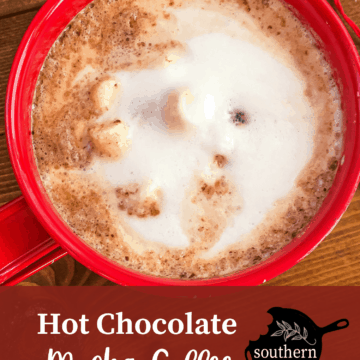 A red mug of hot chocolate topped with steamed milk on a wooden background surrounded by spilled coffee beans with overlay text.