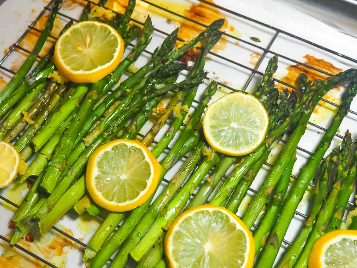 Zoomed in cooked lemon asparagus on a cooling rack.