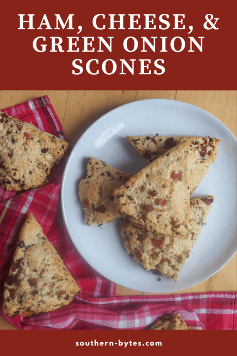 A pin image of a plate of ham and cheese scones with green onions.