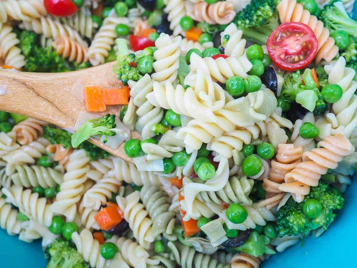 A scoop of pasta salad on a wooden spoon.