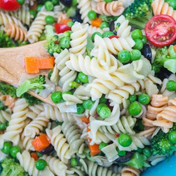 A bowl of pasta salad and a wooden spoon, zoomed in.
