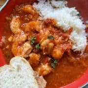 A red bowl of shrimp creole with rice and french bread.