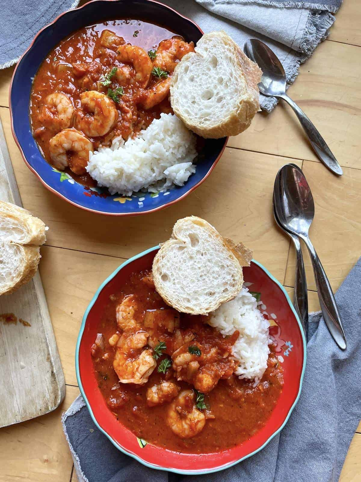 Two bowls of shrimp creole, one red and one blue, with french bread and rice with three spoons.