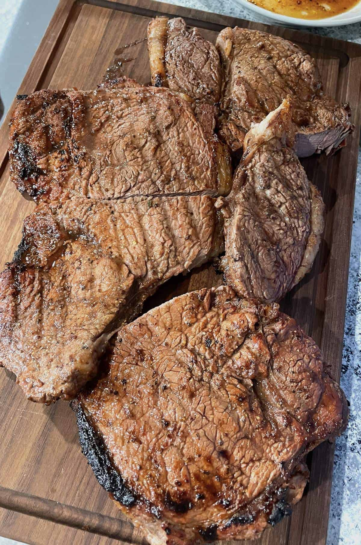 Two steaks on a wooden cutting board cut into large pieces.