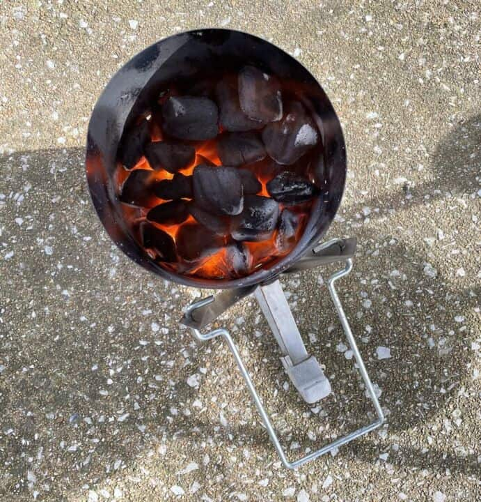 Coals in a charcoal grill starter lit on fire.