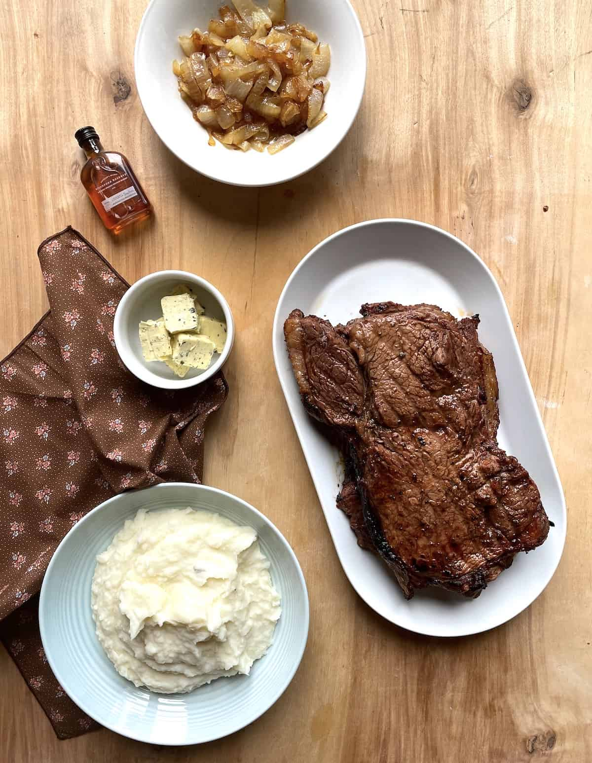 A steak on a white plate, a bowl of mashed potatoes, a bowl of herbed butter, and a bowl of fried onions.