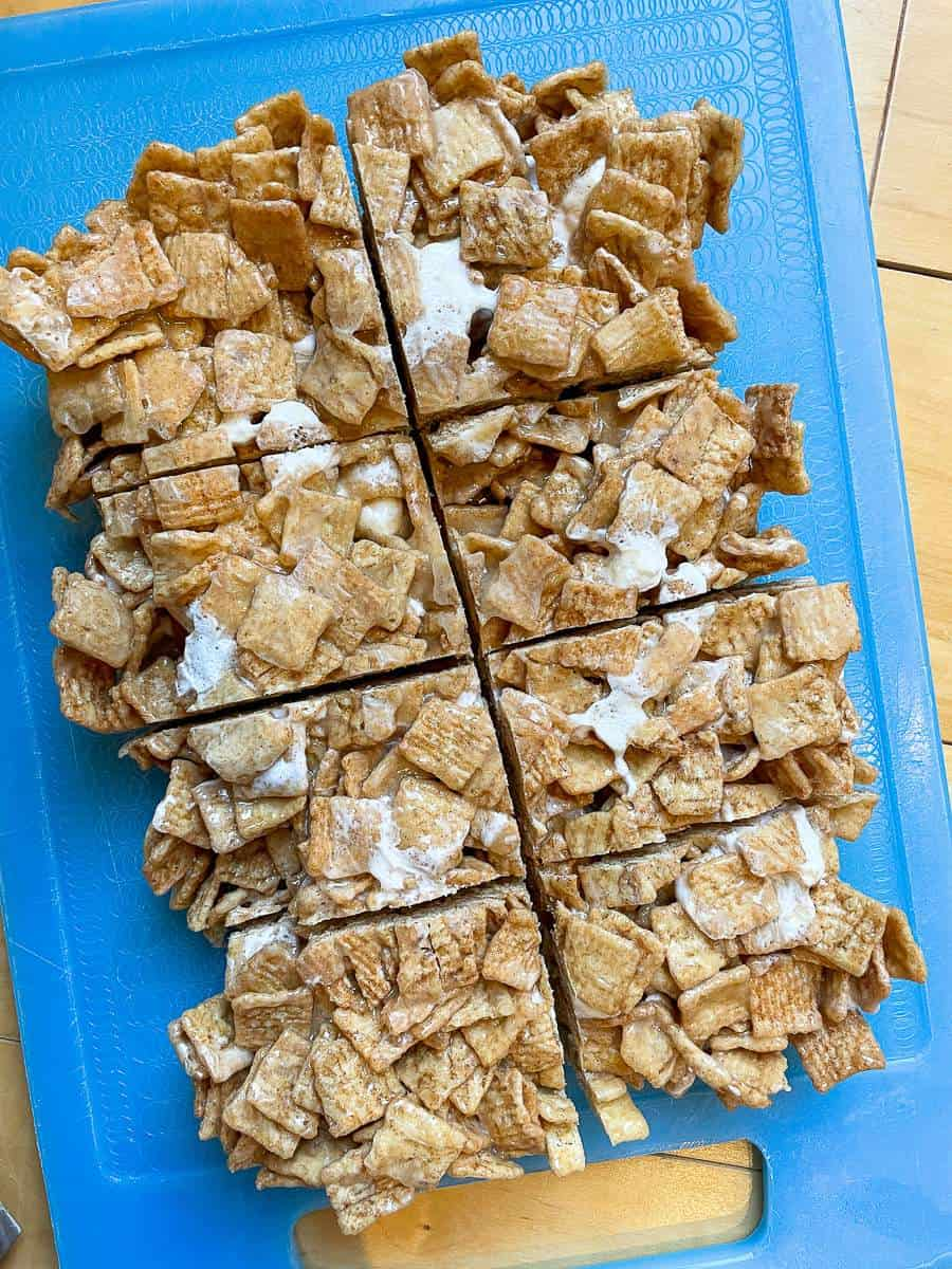 Cinnamon Toast Crunch Cereal Treats sliced into squares on a blue cutting board.